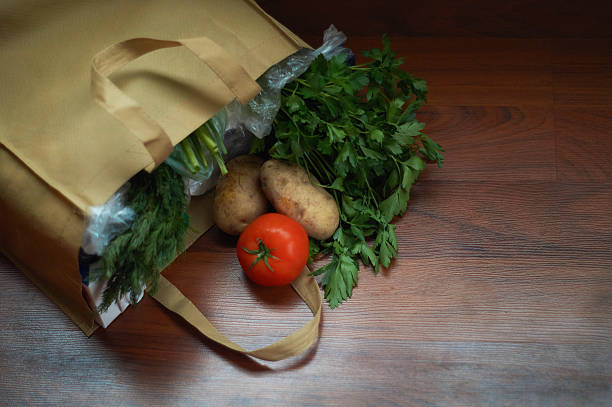 groceries and fresh produce in bag on wood floor stock photo
