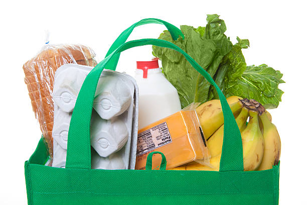 groceries in a green reusable shopping bag stock photo