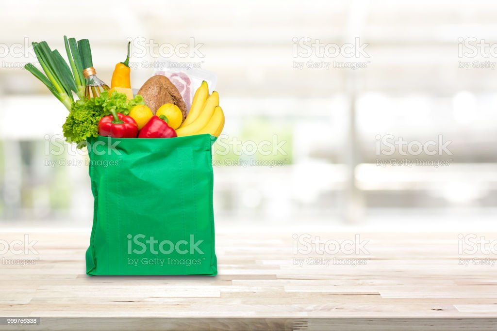 Groceries in green reusable shopping bag on wood table stock photo