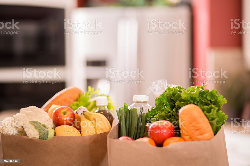 Groceries in paper bags on counter in home kitchen. stock photo