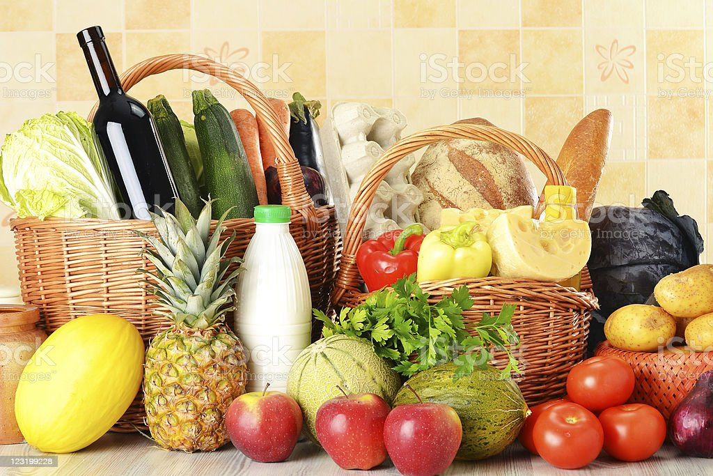 Groceries in wicker basket on kitchen table royalty-free stock photo