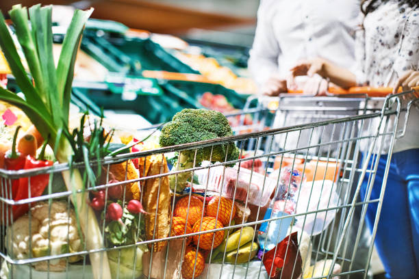 Groceries shopping. Unrecognizable young couple with a full shopping cart of groceries at a convenience store. full stock pictures, royalty-free photos & images