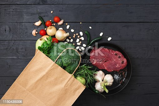 1126188273 istock photo Grocery bag top view with healthy food on wooden background top view 1150435006