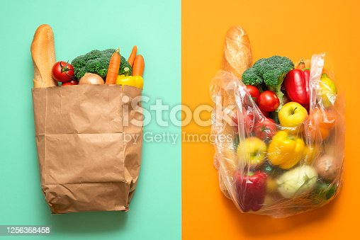 Top view with groceries in plastic and paper bags on a bicolored background. Concept for plastic-free shopping. Choosing between paper and plastic bags.