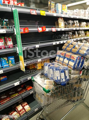 Grocery cart in a supermarket with stocks of rice and other cereals next to half-empty shelves. Food panic because of Coronavirus COVID-19. St. Petersburg, Russia. 2020-03-18.
