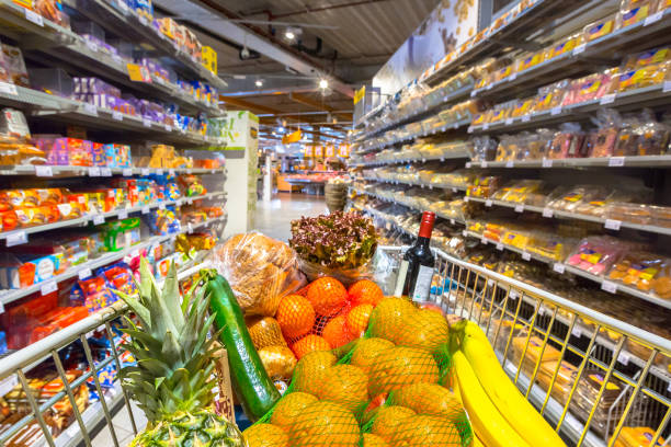 Grocery cart in supermarket Grocery cart in supermarket filled with food products seen from the customers point of view full stock pictures, royalty-free photos & images