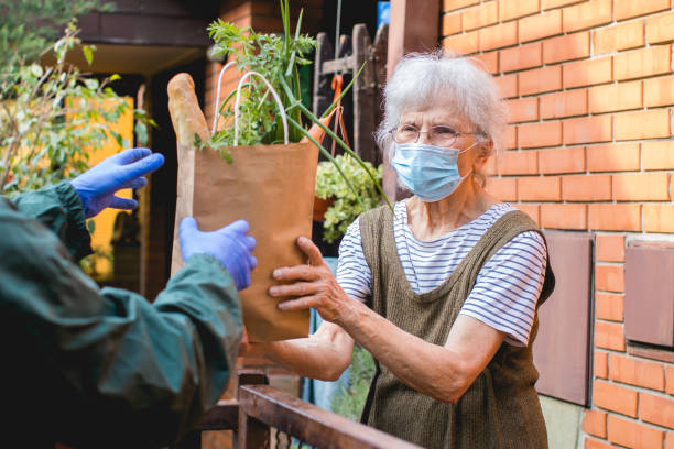grocery delivery to senior woman during pandemic stock photo