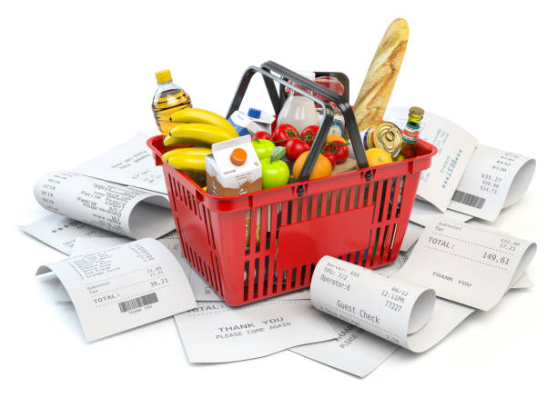 Grocery expenses budget  and consumerism. Shopping basket with foods on the pile of receipt isolated on white. stock photo