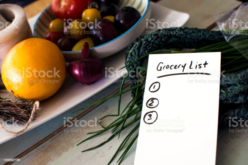 Grocery list for doing groceries on kitchen counter with superfood kale  and citrus fruit with vegetables stock photo