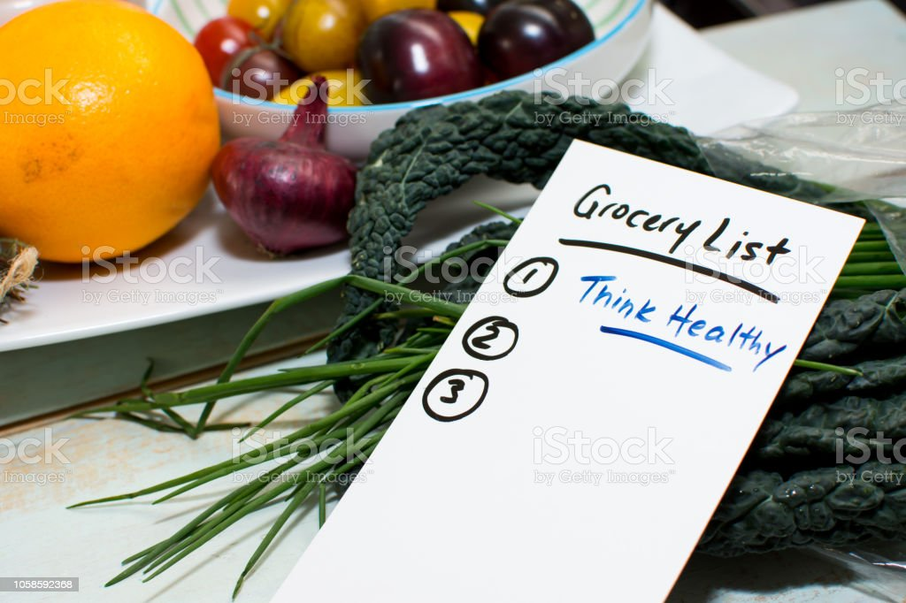 Grocery list on rustic wood counter with fresh fruits and vegetables conceptual healthy organic food  and lifestyle  concept stock photo