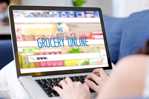 Grocery online shopping, laptop computer screen with www. on search bar website, woman hand searching web page for grocery shopping online, business, E-commerce, digital marketing stock photo