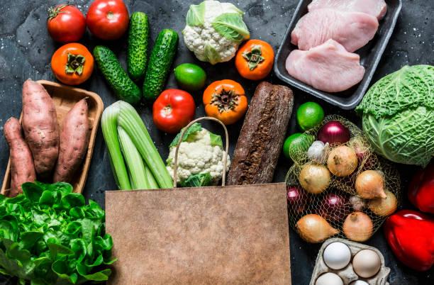 Lebensmittel-Papiertüte mit frischem Bio-Gemüse, Obst, Fleisch auf dunklem Hintergrund, Ansicht von oben. Gesunde Ernährung Lebensmittel Konzept – Foto