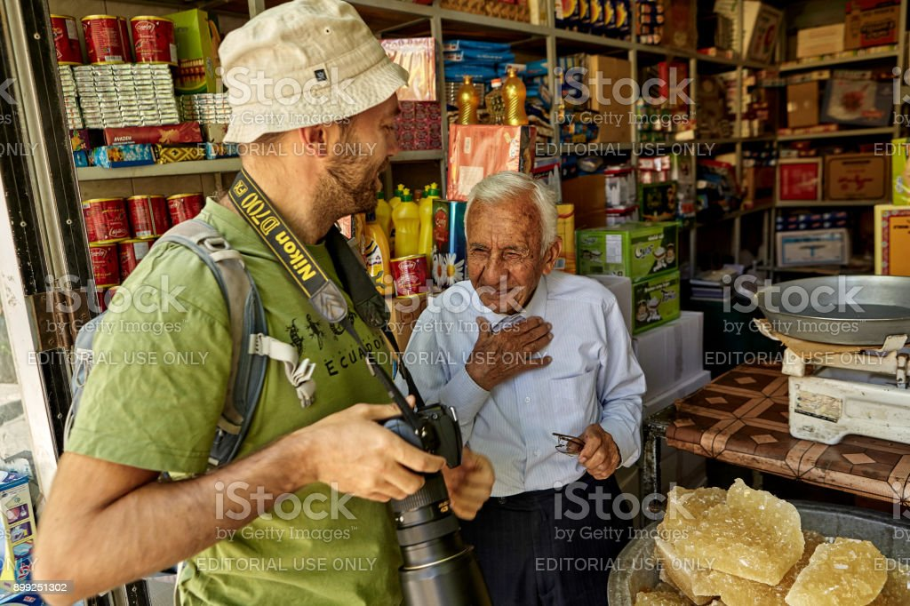 Grocery seller talks to traveler in interior of store, Iran. stock photo