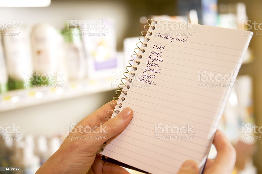 Grocery Shopper Checking Her List at the Store stock photo