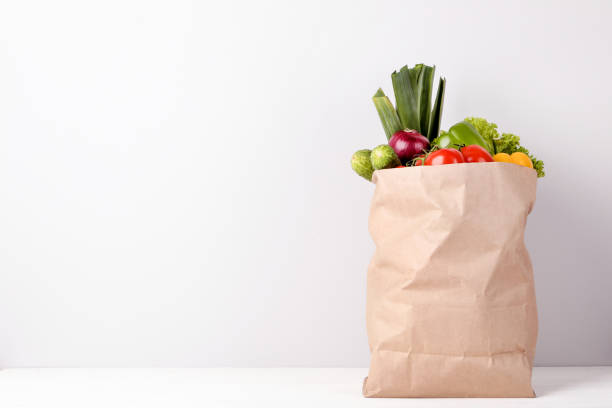 Grocery shopping bag with food on gray background Grocery shopping bag with food on gray background bag stock pictures, royalty-free photos & images