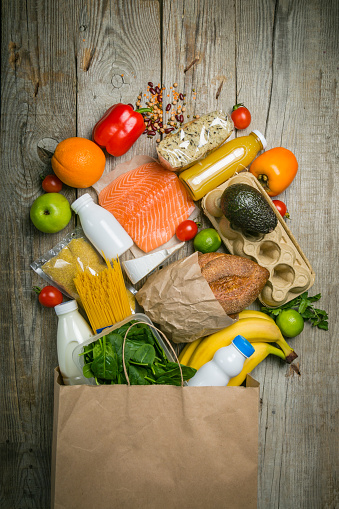 istock Grocery shopping concept. Balanced diet concept. Fresh foods with shopping bag on rustic wood background 920931634