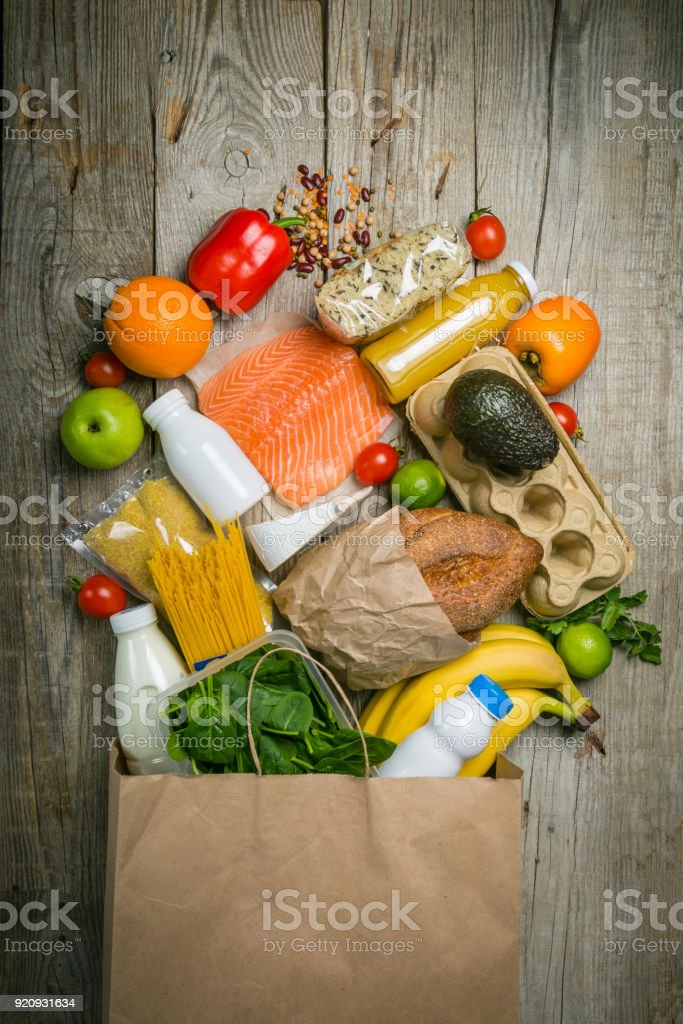 Grocery shopping concept. Balanced diet concept. Fresh foods with shopping bag on rustic wood background stock photo