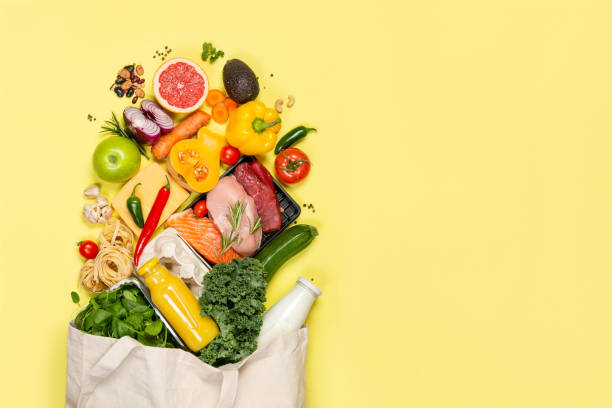 Grocery shopping concept - foods with shopping bag Grocery shopping concept - meat, fish, fruits and vegetables with shopping bag, top view supermarket stock pictures, royalty-free photos & images