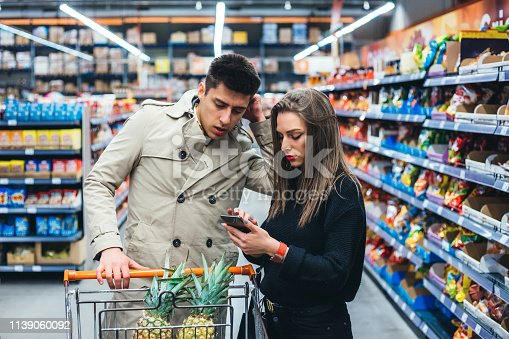 Young couple is grocery shopping at a supermarket aisle