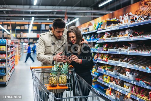 Young couple in grocery shopping at a supermarket aisle using phone.