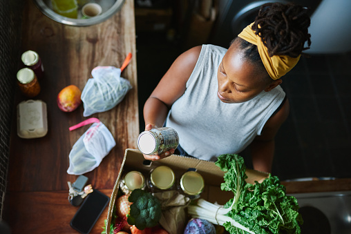 High angle shot of a young woman unpacking her groceries in the kitchen at home