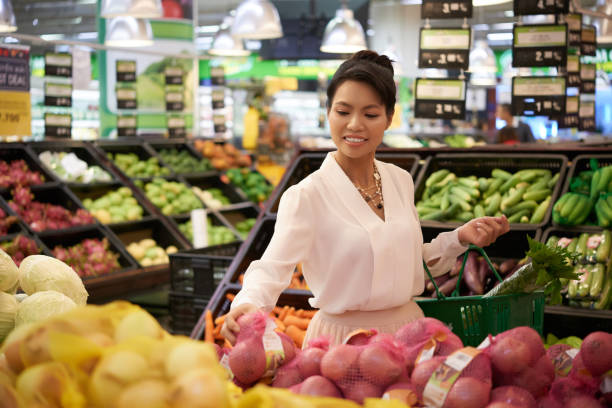 Grocery shopping Beautiful elegant Vietnamese woman buying fruits and vegetablet in supermarket vietnamese ethnicity stock pictures, royalty-free photos & images