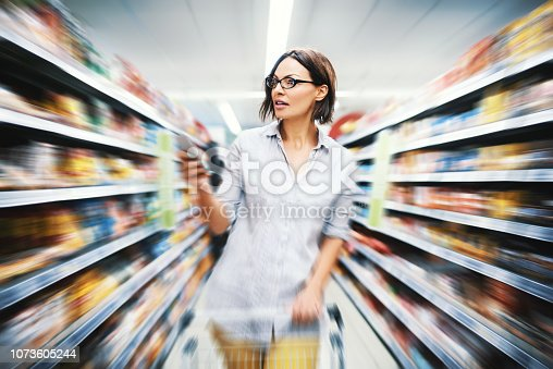 Attractive woman searching for food in a supermarket from a checklist on her phone. Motion blur background.