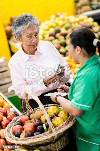 Grandmother paying for her grocery shopping