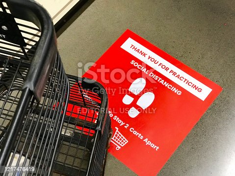 U.S. Grocery store checkout line notification signs for COVID-19 Social Distancing advising customers to distance each others to prevent COVID-19 Virus infection for health and safety.