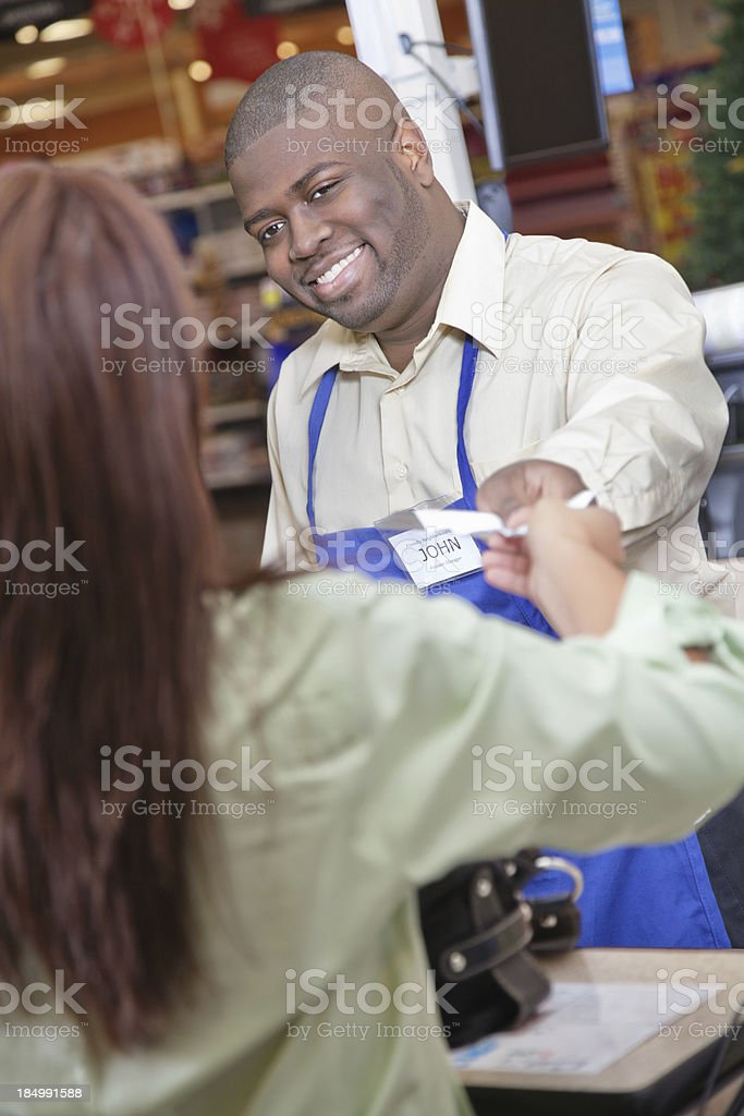 Grocery store checkout worker handing receipt to purchasing customer royalty-free stock photo