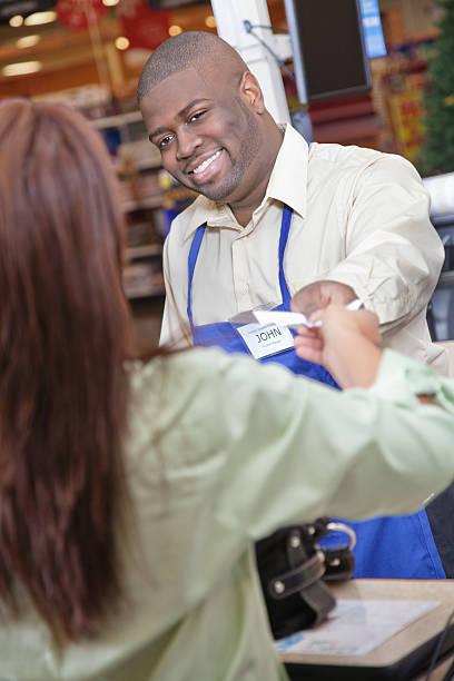 lebensmittelgeschäft-check-out-arbeiter an purchasing kunden den kassenbeleg zwecke - kassenbon stock-fotos und bilder