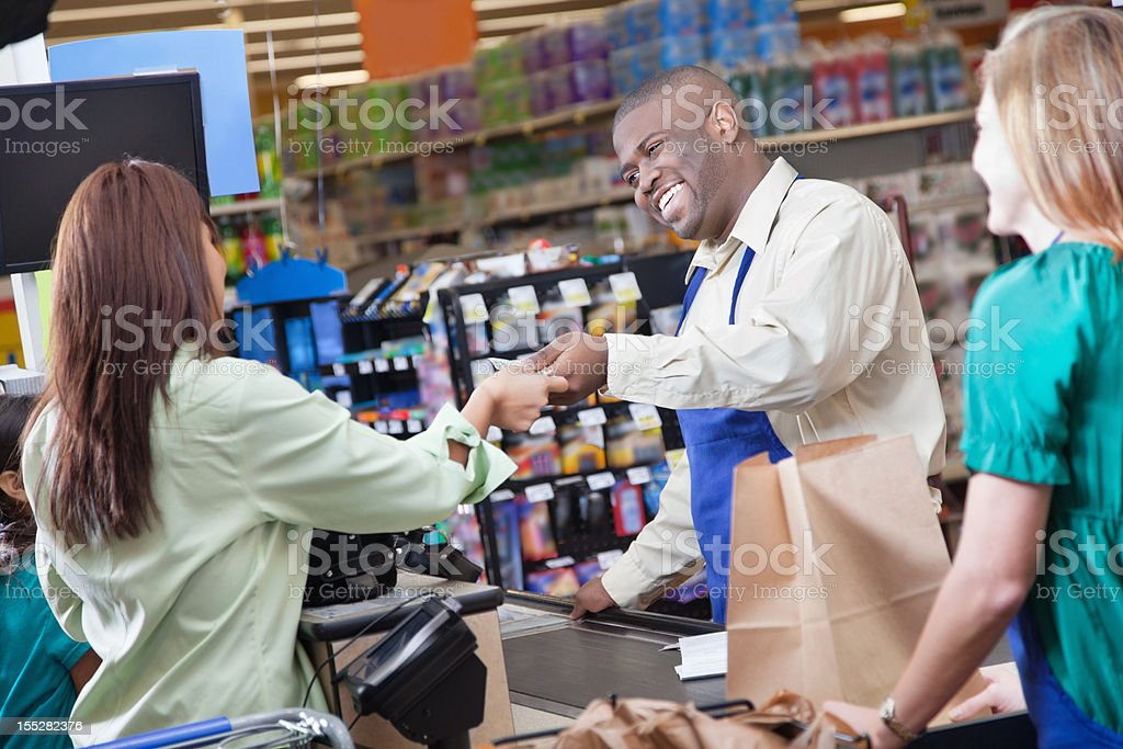 Grocery store clerk handing taking payment from customer stock photo