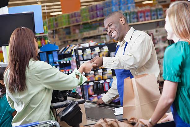 lebensmittelgeschäft clerk ausführender nimmt zahlungen von kunden - kassenbon stock-fotos und bilder