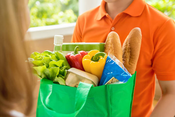 Grocery store delivey man  delivering food to a woman at home stock photo