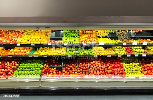 A display of fresh produce in a retail refrigerator case in grocery store. A variety of fresh fruits are presented to customers.