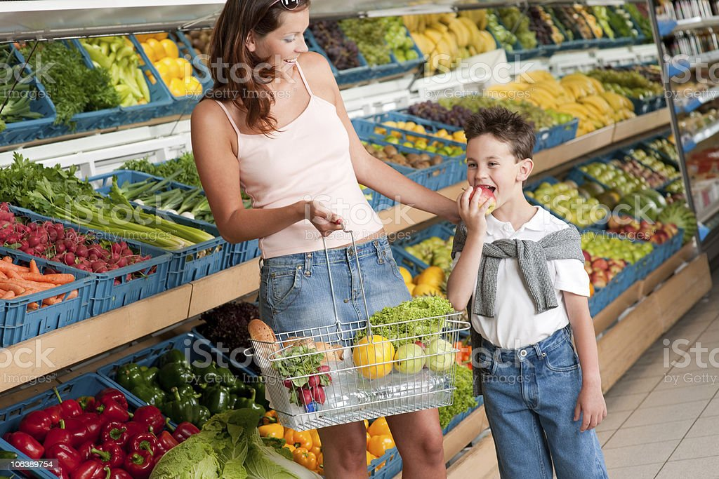 Grocery store - Woman with child shopping in supermarket royalty-free stock photo