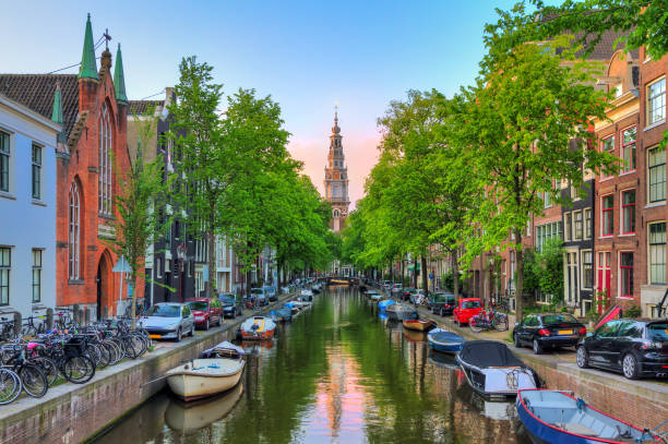 Groenburgwal in spring Beautiful Groenburgwal canal in Amsterdam with the Soutern church (Zuiderkerk) at sunset in summer canal stock pictures, royalty-free photos & images