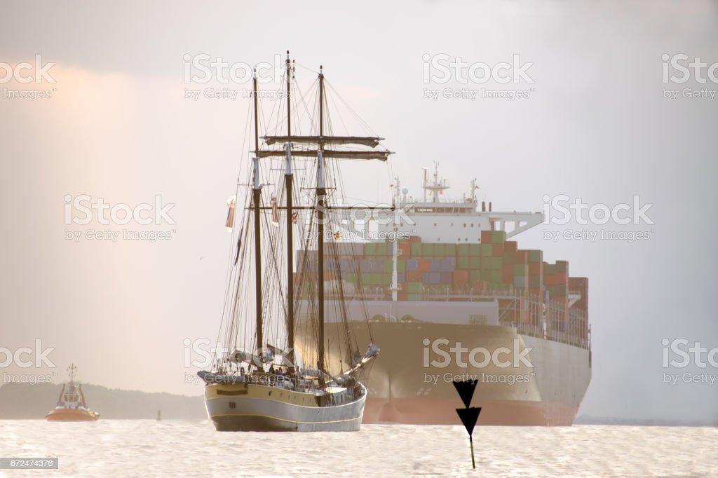 großes Containerschiff mit Segelyacht davor stock photo