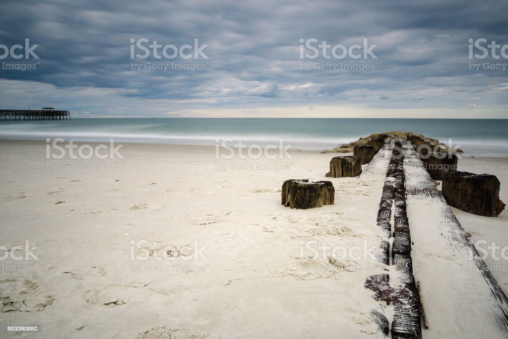 groin and pier on a beach in South Carolina stock photo