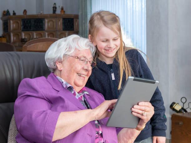 großmutter, die dachmarke enkelkind etwas lustiges auf dachmarke tablet weitergeleitet - lila mädchen zimmer stock-fotos und bilder