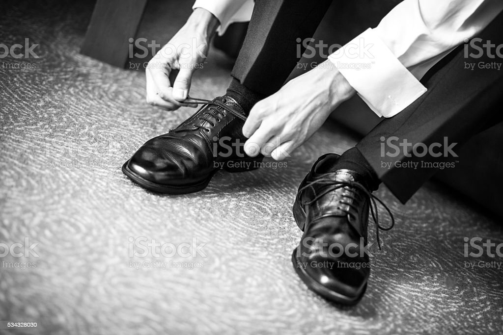 groom agrees shoes on wedding day stock photo
