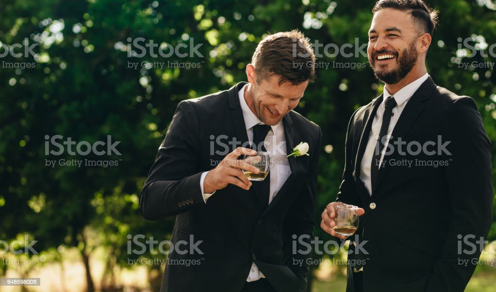 Groom and best man drinking at wedding party stock photo