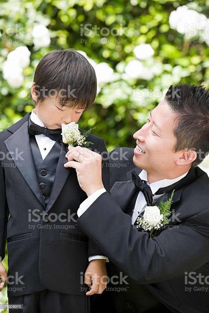 Groom and boy smelling flower stock photo