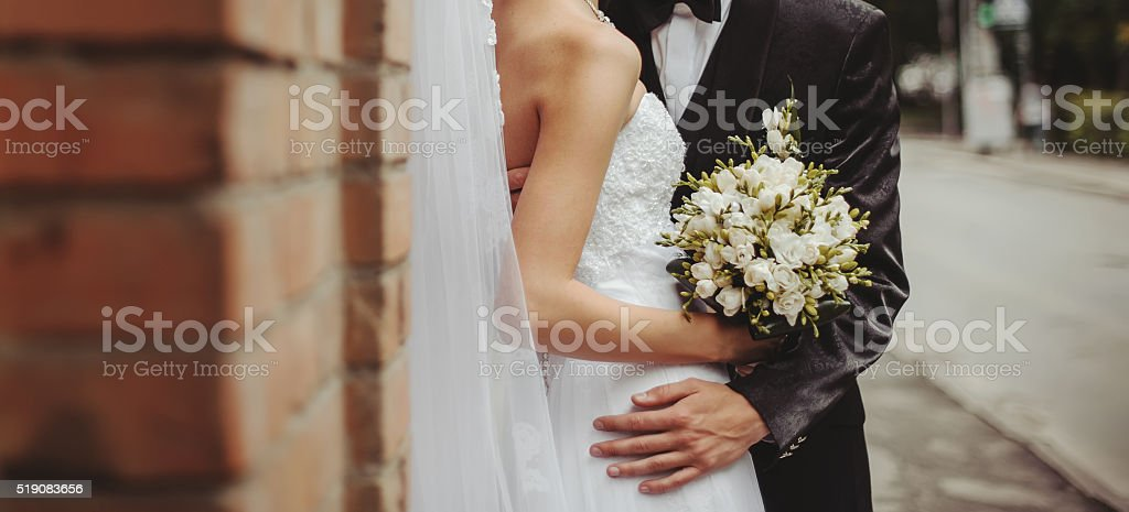 Groom and Bride embracing next to red brick wall. stock photo