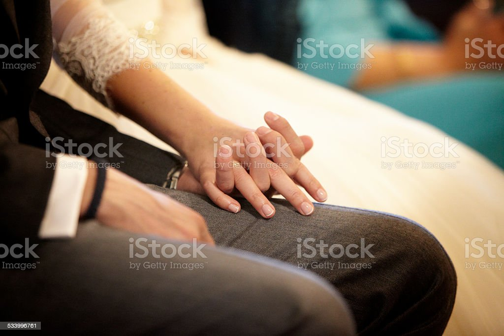 Groom and bride holding hands during their wedding ceremony stock photo