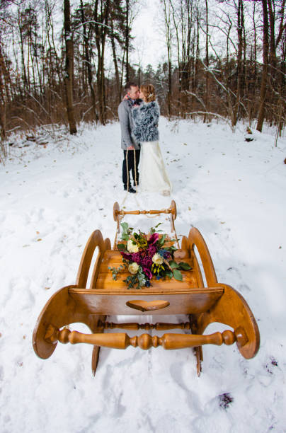 groom and bride in the winter forest with the sled - brautstrauß aus holz stock-fotos und bilder