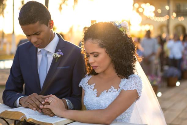 bräutigam und braut kniend beten - hochzeitsfrisur twilight stock-fotos und bilder