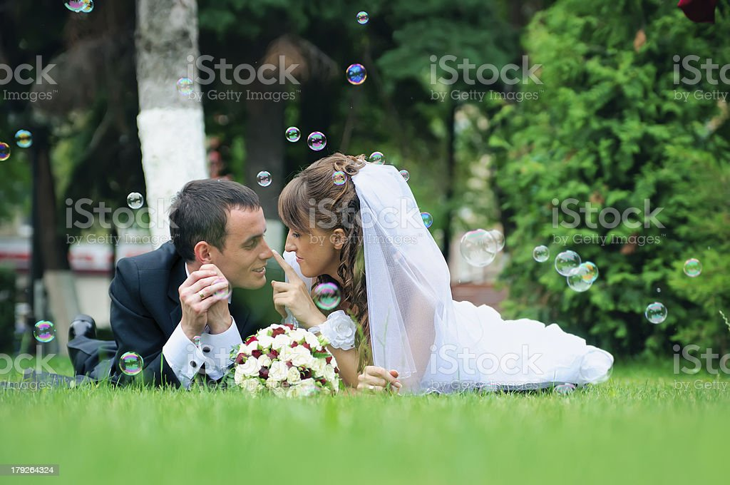 groom and bride lie on a grass around soap bubbles royalty-free stock photo