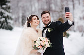 Groom and bride make a selfie on their wedding day. Newlyweds in winter.