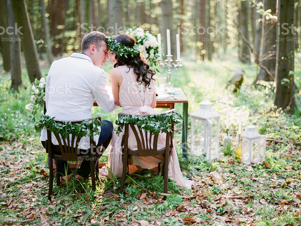 Groom and bride sitting at the table setted for two stock photo